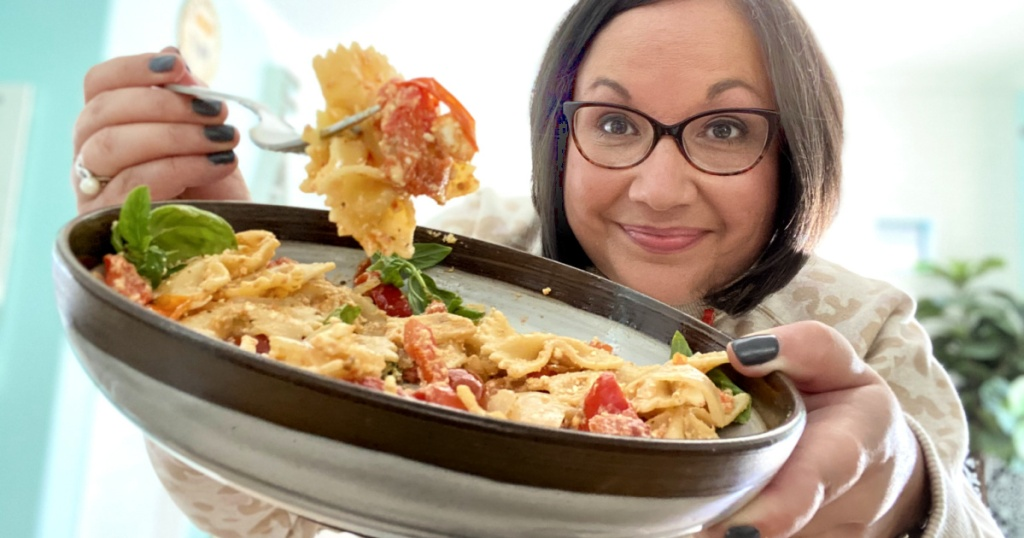 woman holding up a bowl of pasta