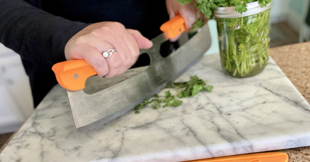 woman mincing herbs with pizza slicer