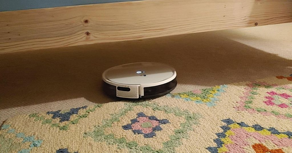 white robot vacuum cleaning under bed
