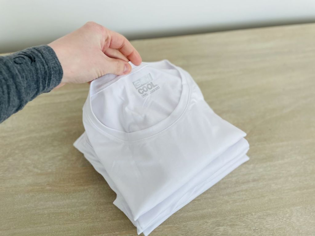 hand holding a stack of t-shirts