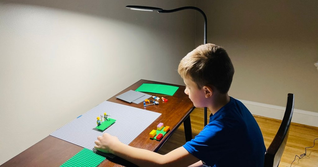 boy sitting at desk with lego set and floor lamp shining over him