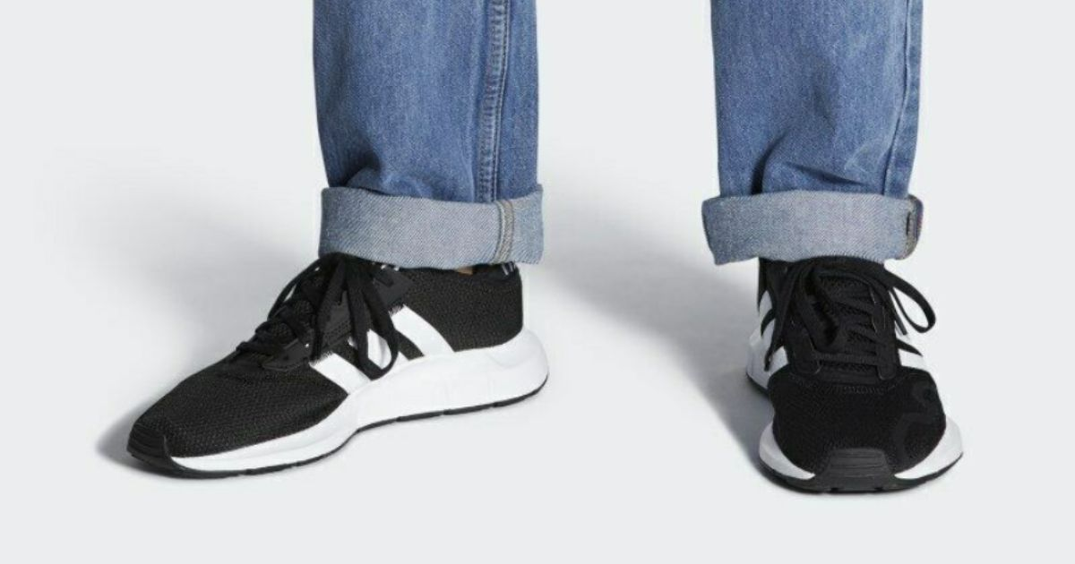 person in jeans wearing Adidas Men's Originals Swift Sneaks