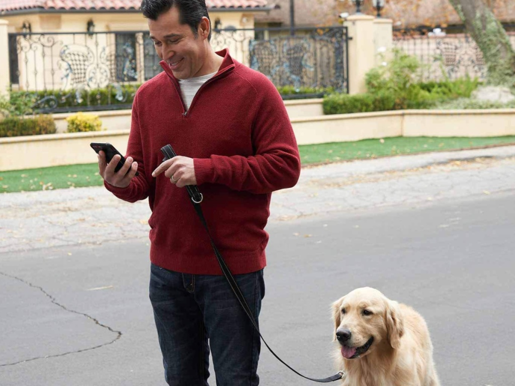 Man walking a dog outside looking at his smartphone