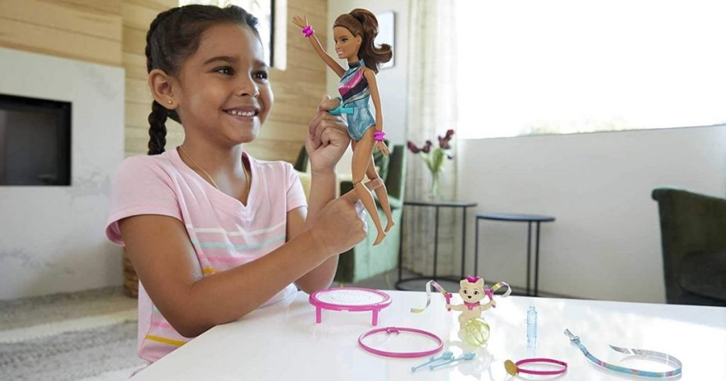 Girl playing with Barbie Adventures Gymnast