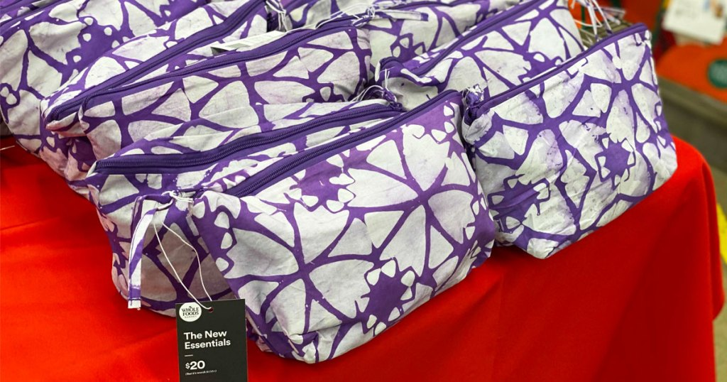 purple and white cosmetics bags on a red table