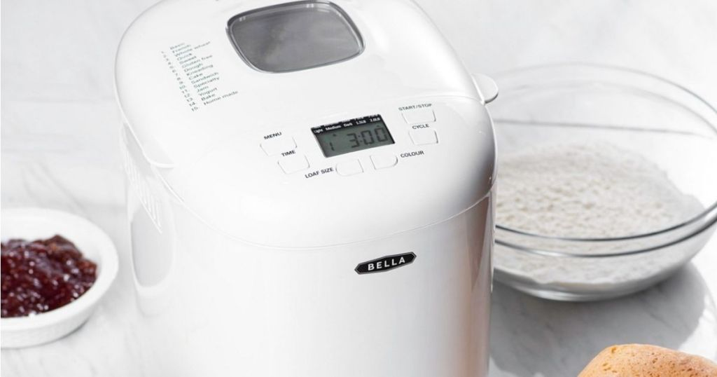 bread maker with ingredients and bread by it