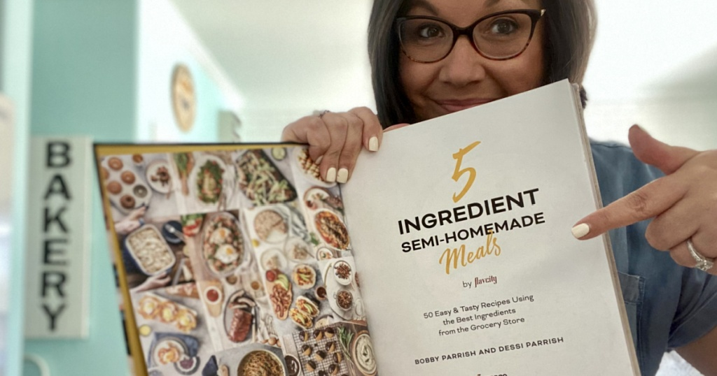 woman holding 5-ingredient semi-homemade meals cookbook