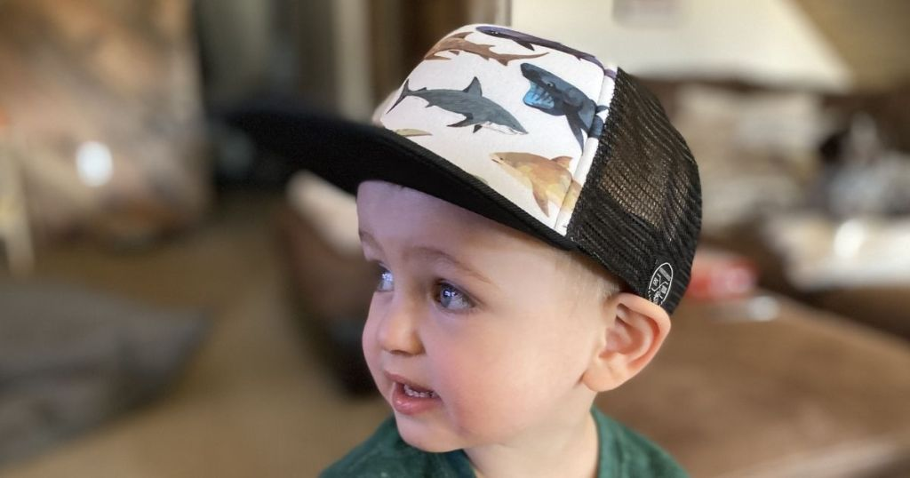 child wearing a hat with fish on it