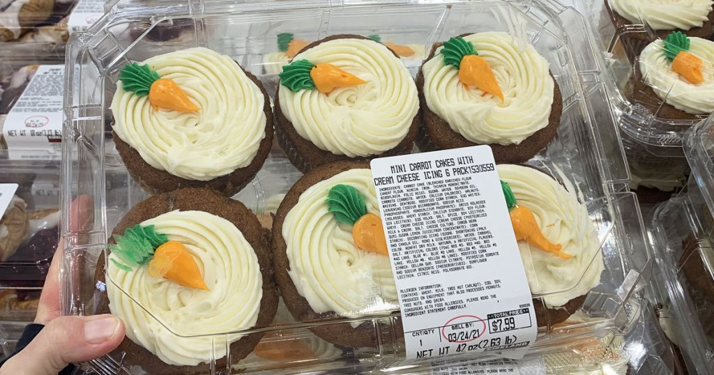 person holding package of carrot cake cupcakes at costco