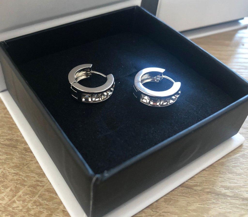 two white gold hoop earrings in black box