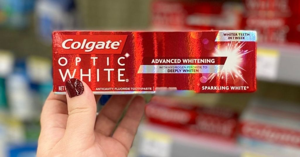 hand holding Colgate Optic White Toothpaste