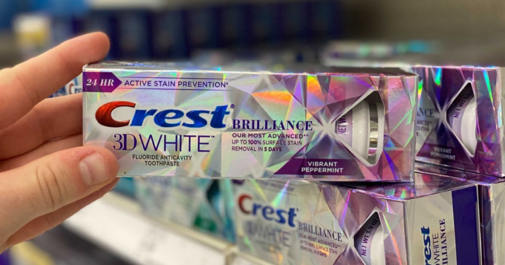 hand holding out Crest 3D White Brilliance Toothpaste