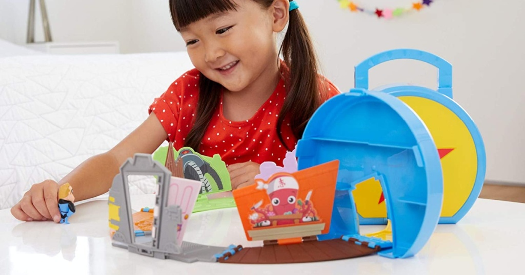 girl playing with Disney mini playset on table