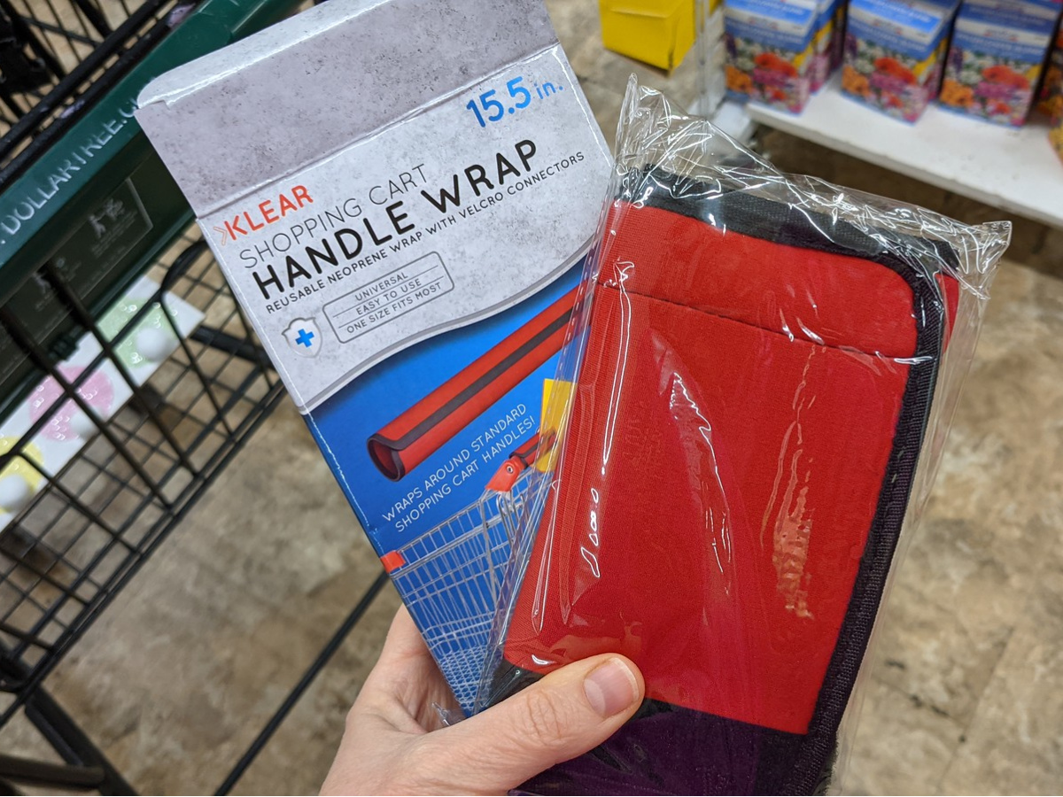 hand holding a shopping cart handle wrap in and out of packaging