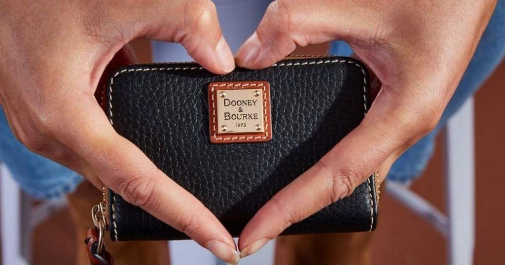 hand making a heart holding Dooney & Bourke Wallet