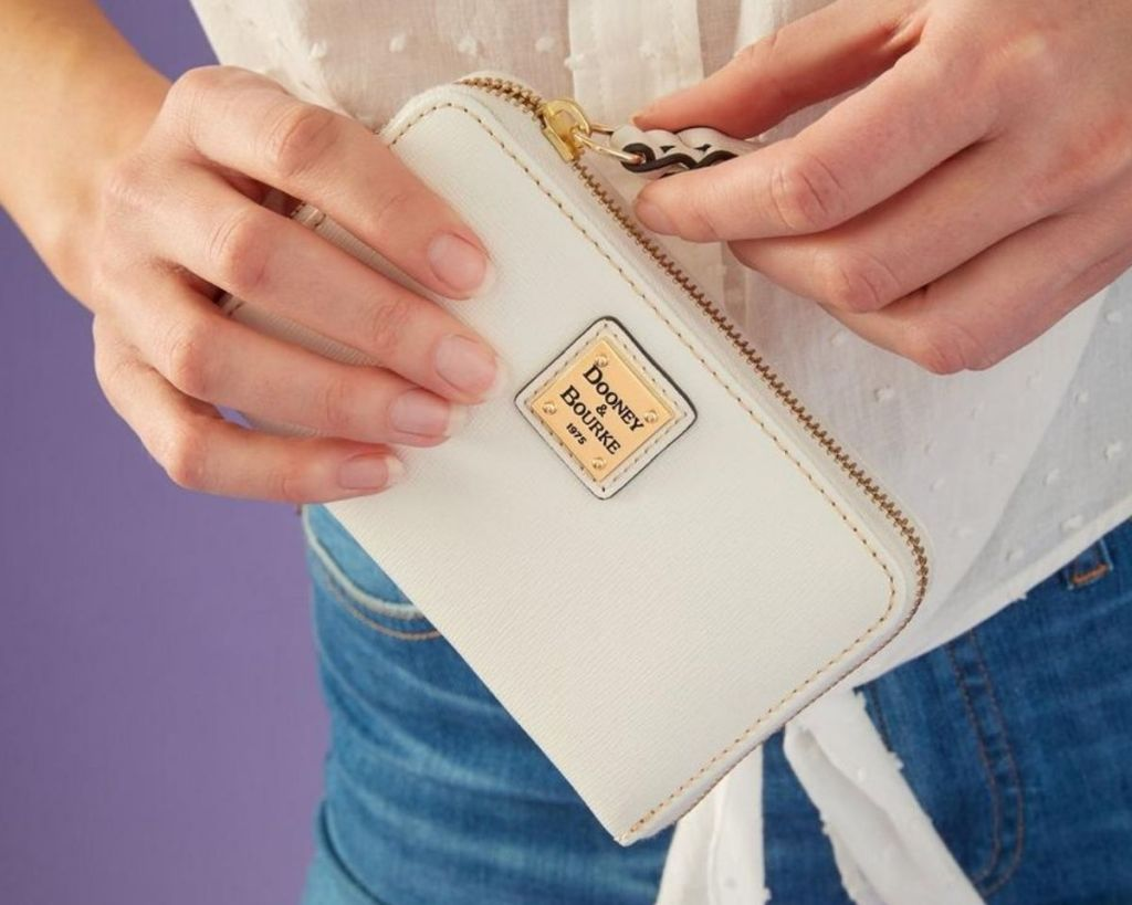 lady holding white Dooney & Bourke Wallet