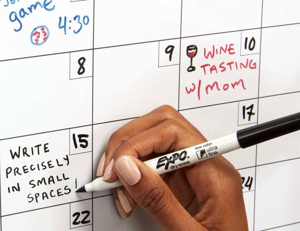 person writing on a white board calendar with thin expo marker
