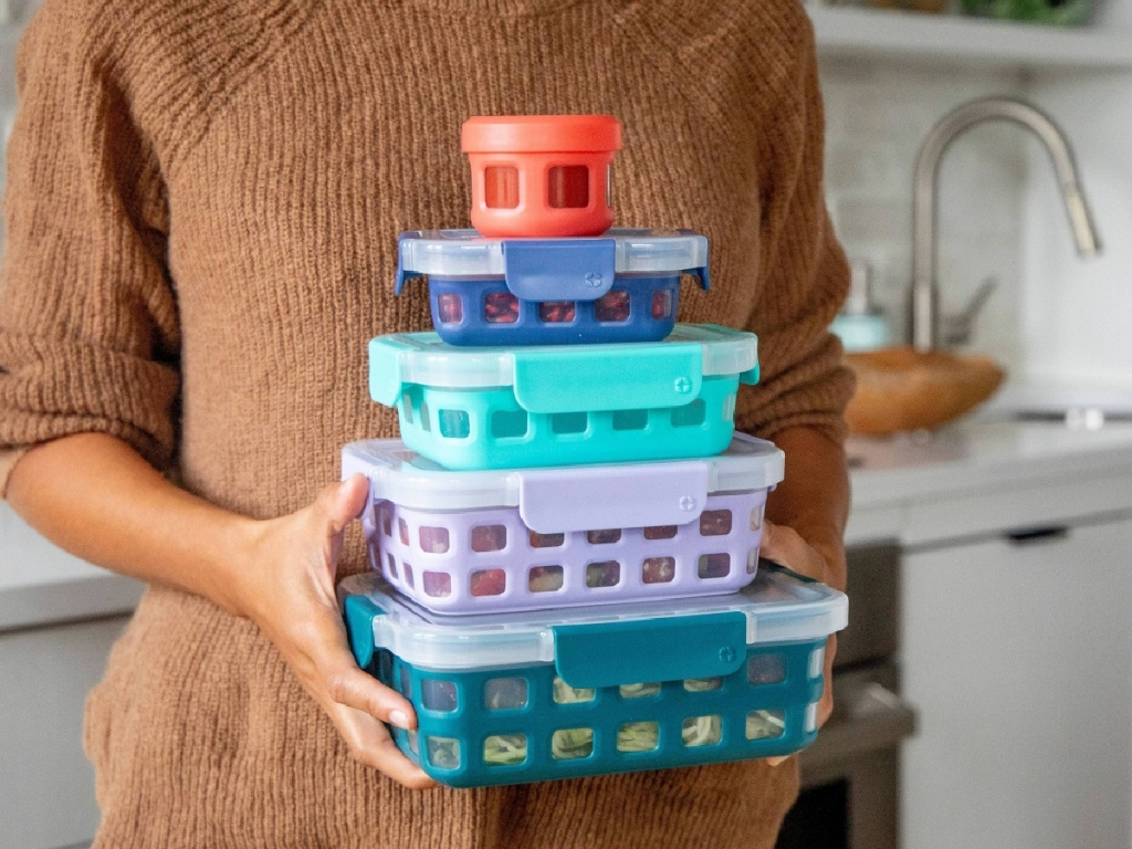 woman in kitchen holding five colored food storage containers