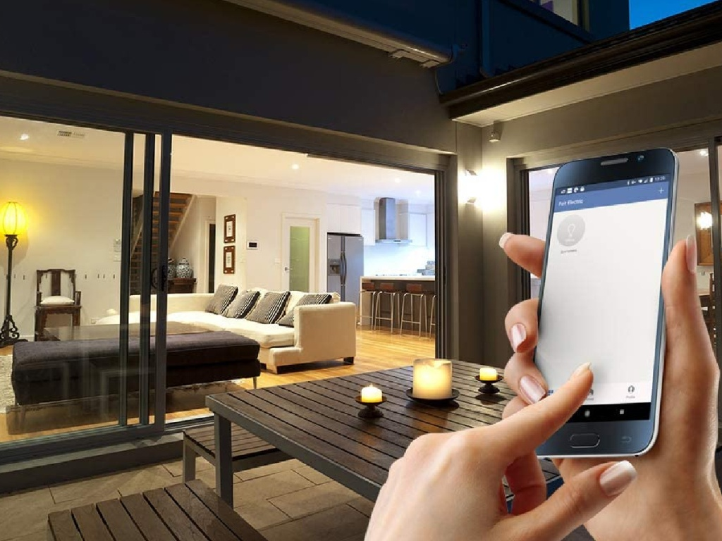 hand holding a smartphone with a mobile app controlling the lights in a home