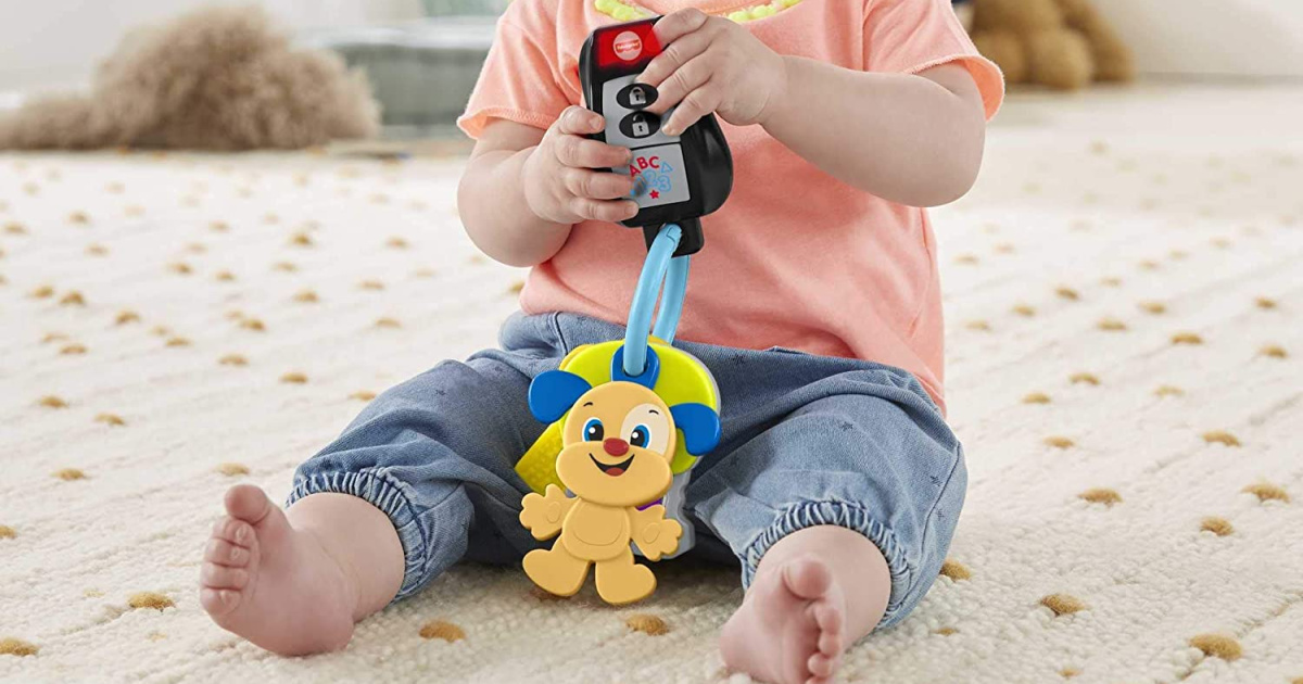 Baby holding a key themed toy while sitting on the floor