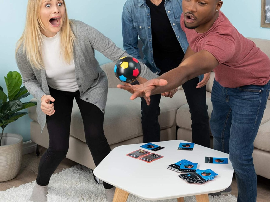 two men and women playing game with cards and ball in living room