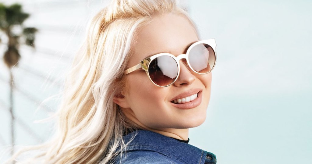 woman with blonde hair wearing a pair of gold rimmed sunglasses