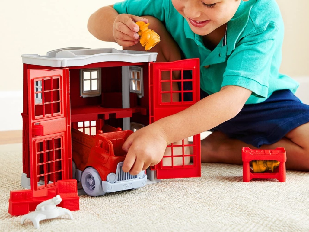 little boy sitting on the floor playing with green toys fire station