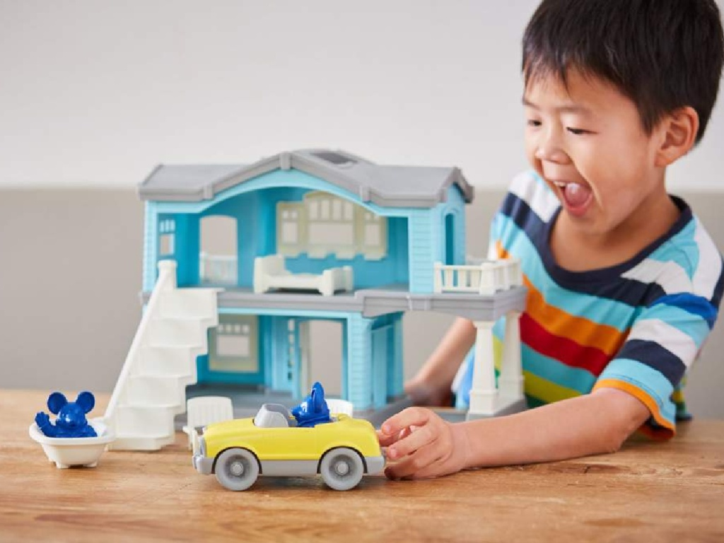 little boy playing with a green toys house and car