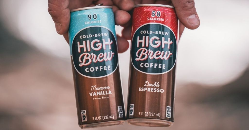 two hands holding High Brew Coffees