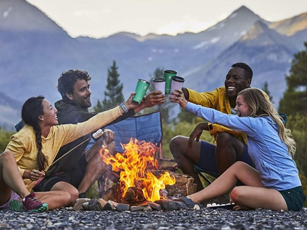 2 men and two women cheersinHydro Flask 22oz Tumblers over a bonfire