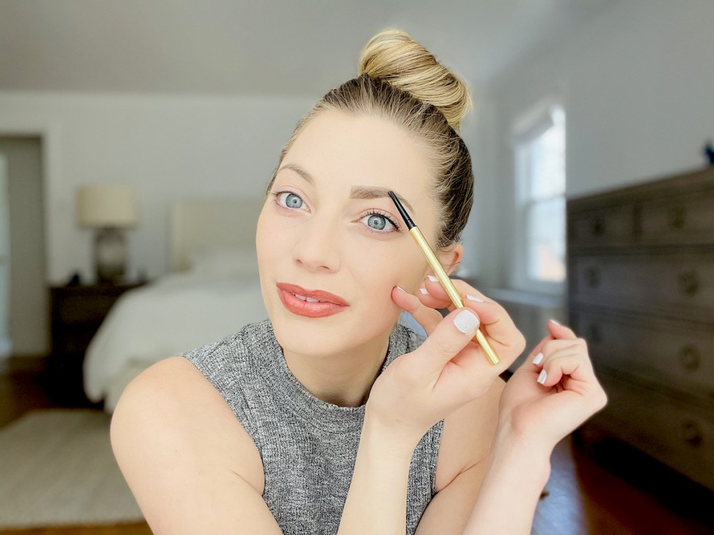 woman drawing on eyebrow with gold winky lux eyebrow pencil