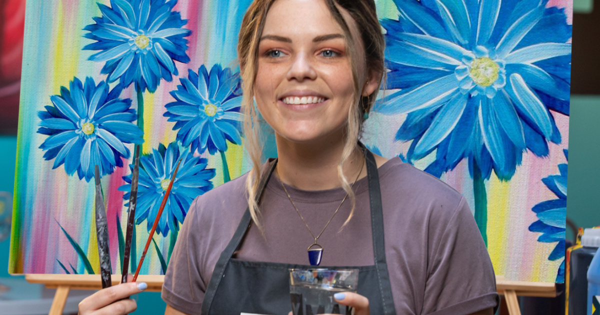 girl wearing a paint smock in front of a floral painting