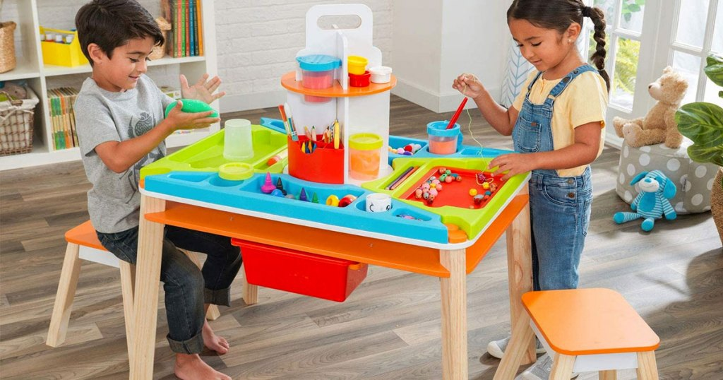 two kids playing at creation station table in playroom