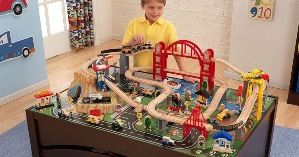 boy playing at a train table