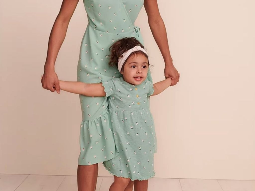 woman holding girls hands both in matching outfits