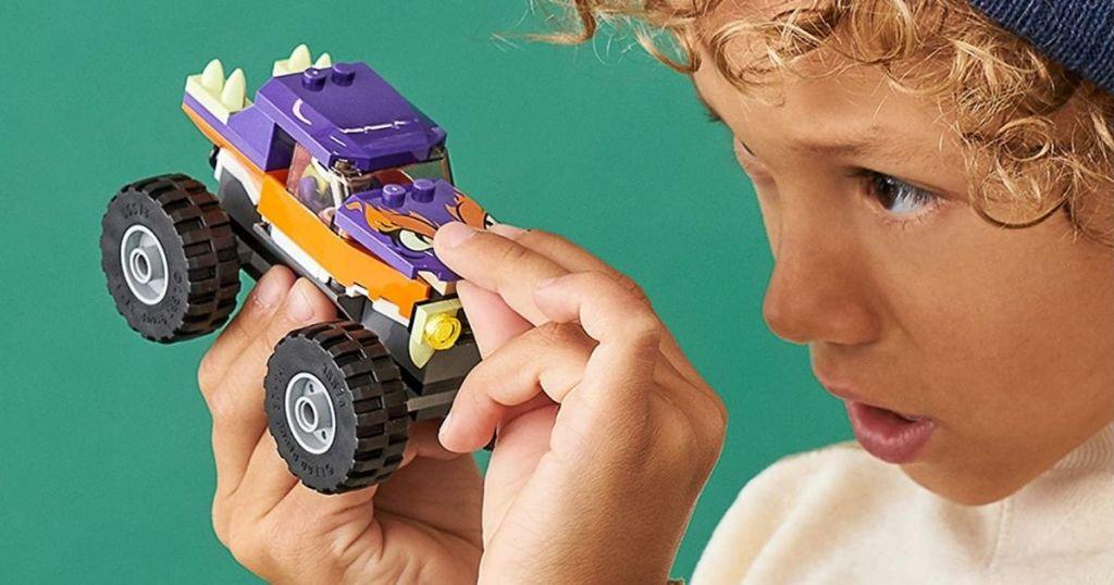boy holding a LEGO monster truck
