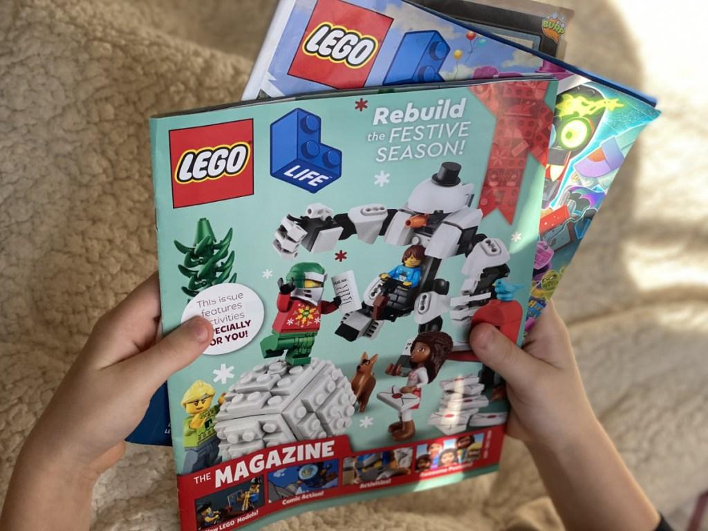 hands holding lego magazines