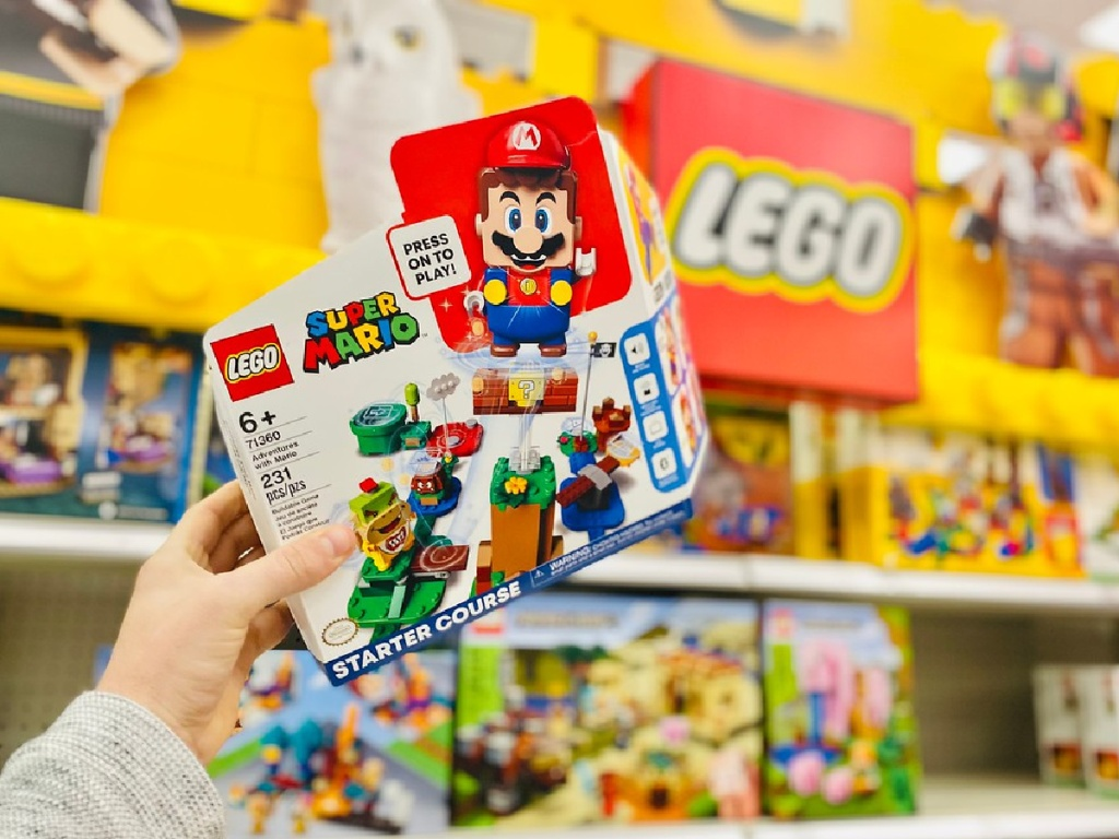 man's hand holding LEGO Super Mario kit in front of LEGO sign in store