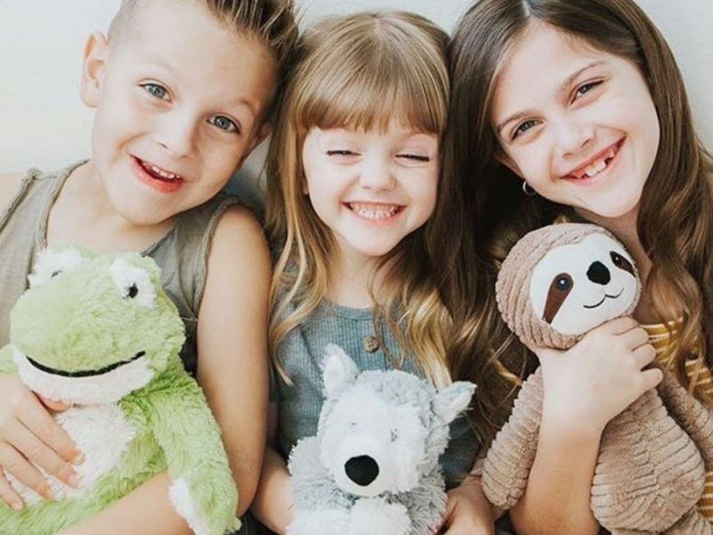 three kids with Warmies animals