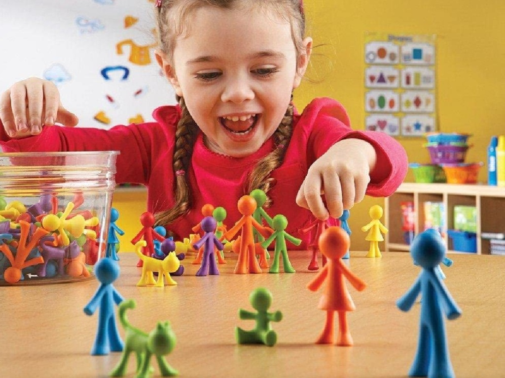 little girl playing with learning resource family counters