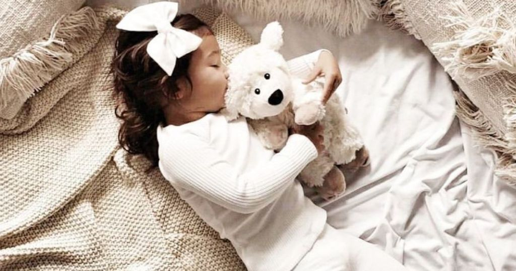 Little girl holding Warmies Comfort Animal
