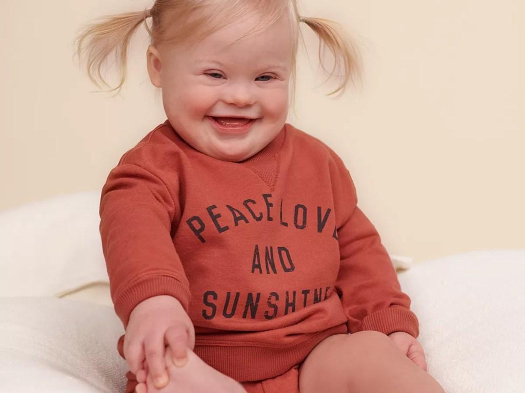baby girl sitting on floor in graphic sweatshirt