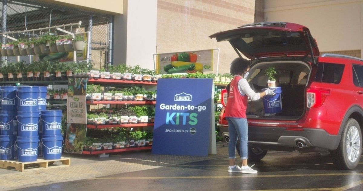 woman loading plants into the back of a vehicle next to lowes signage