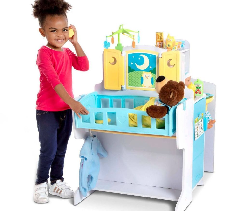 little girl playing next to Melissa & Doug wooden nursery playset
