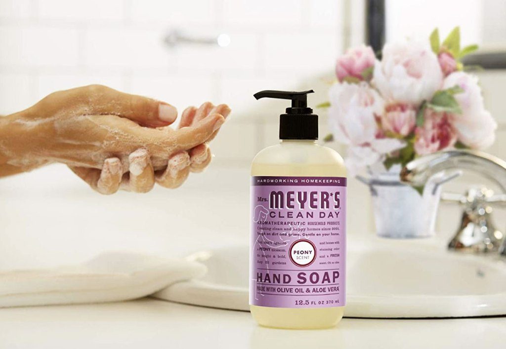 person washing hands next to a bottle of peony mrs meyers hand soap