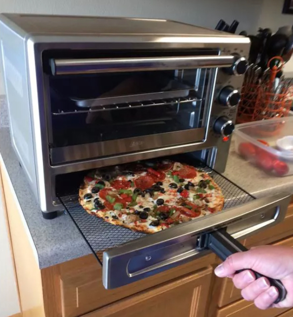 hand pulling out pizza from oster toaster oven drawer