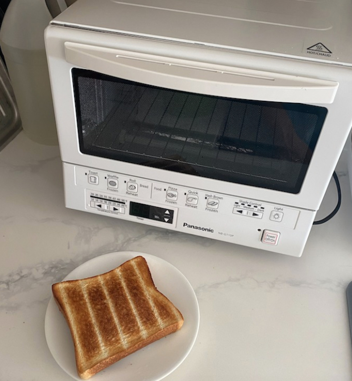 white kitchen appliance on marble counter with piece of toast