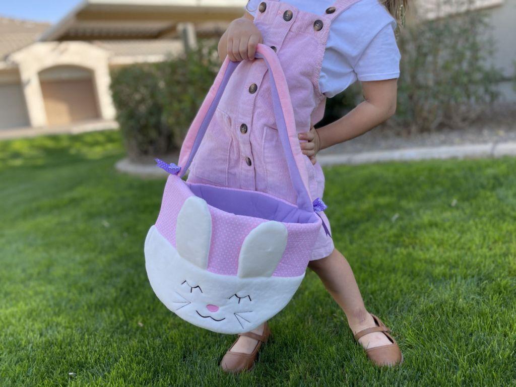 Little girl in pink dress holding large Easter basket