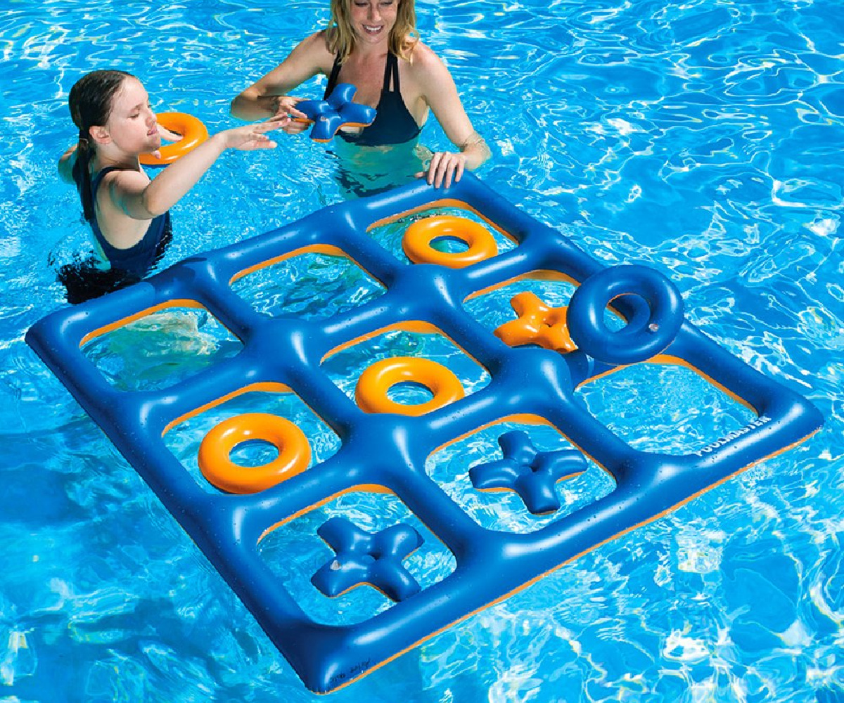 two girls playing with an inflatable tic tac toe board floating in a pool