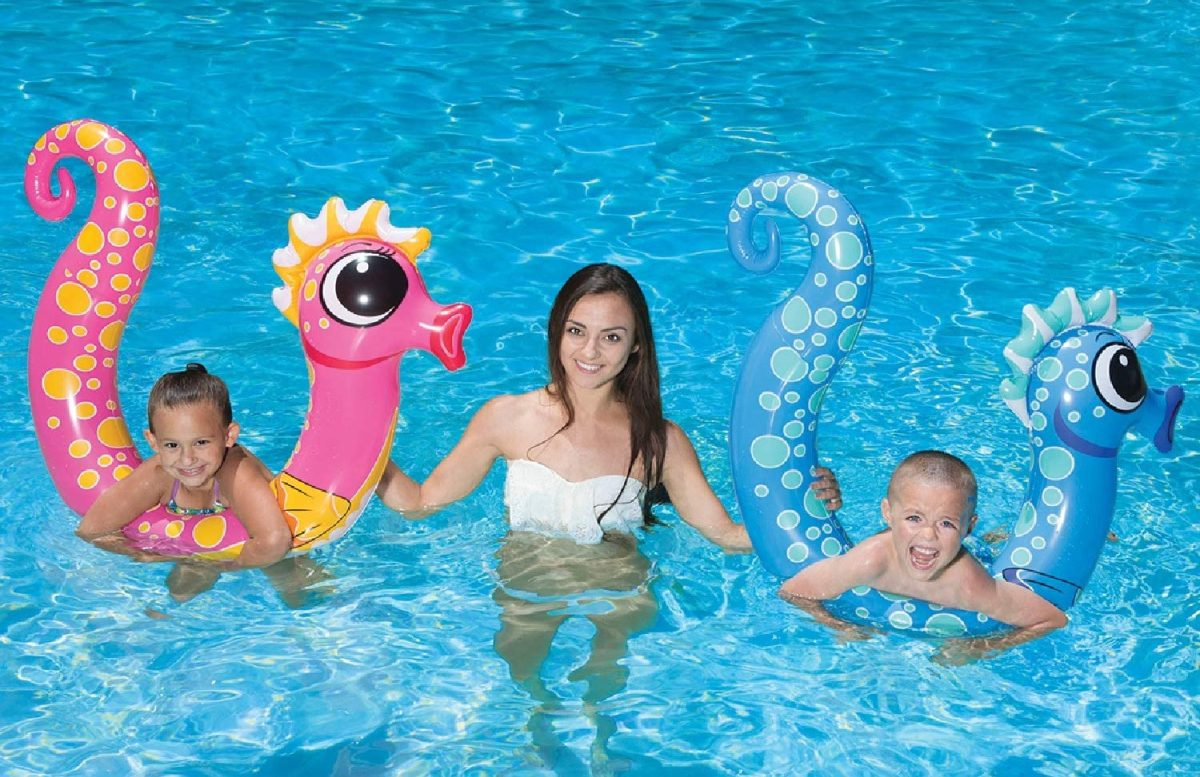 woman in pool with two kids playing on pink and blue seahorse pool noodles